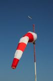 Roter und weißer Windsock mit Flugzeug zur Rückseite. Stockfotos