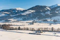 Roter und wei?er Zug, der die schneebedeckten Felder in einer szenischen Winterberglandschaft, Dachstein-Gebirgsmassiv, Liezen-Be stockbild
