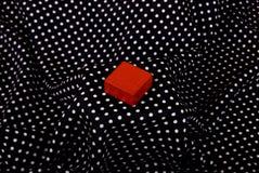 Roter Würfel auf te Schwarzmaterial Lizenzfreie Stockfotografie