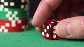 Roter Würfel und Kasino bricht in der Hand auf grüner Tabelle ab stock footage