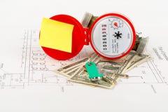 Roter Wasserzähler mit Bargeld und Schlüssel auf Entwurf Stockfotografie