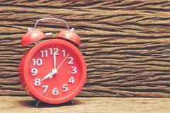 Roter Wecker auf hölzernem altem Hintergrund, rote Uhr bei acht O-` Uhr Lizenzfreie Stockfotografie