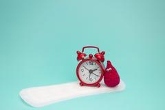 Roter Wecker, Lächelnhäkelarbeitblutstropfen und tägliche Monatsauflage Gesundheitliche Frauenhygiene der Menstruation Kritische  stockfotos