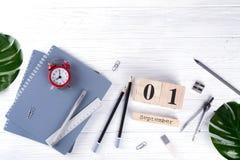 Roter Wecker und Versorgungen, hölzerner Kalender mit Datum am 1. September auf weißem Schreibtisch Zurück zu Schule-Konzept Stockbilder