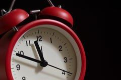 Roter Weckerabschluß oben It' s, das zehn Minuten bis zwölf o&#x27 zeigt; c Stockfoto