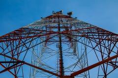 Roter weißer Telekommunikationsturm gegen blauen Himmel - Ansicht von unten Lizenzfreie Stockfotografie