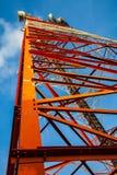 Roter weißer Telekommunikationsturm gegen blauen Himmel - Ansicht von unten Lizenzfreies Stockfoto