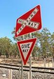 Roter, weißer und schwarzer Bahnübergang und geben Zeichen nach Stockbilder