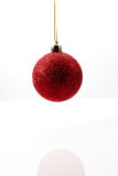 Roter Weihnachtsball, der im mitten in der Luft gegen einen weißen Hintergrund hängt Stockbild