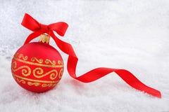 Roter Weihnachtsball mit Band im Schnee Lizenzfreie Stockfotos