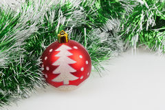 Roter Weihnachtsball mit gemaltem Weihnachtsbaum und grüner Girlande Stockbild
