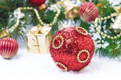 Roter Weihnachtsball mit Tannenzweigen und Dekorationen Stockbild