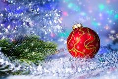 Roter Weihnachtsball und -Baumast auf dem Hintergrundlichter garl Lizenzfreie Stockbilder