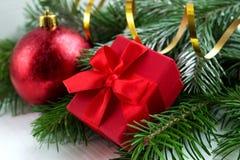 Roter Weihnachtsball und -geschenk mit Tannenzweigen Lizenzfreies Stockbild