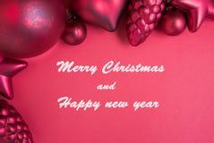 Roter Weihnachtsball und -verzierung auf rotem Hintergrund Lizenzfreie Stockfotografie