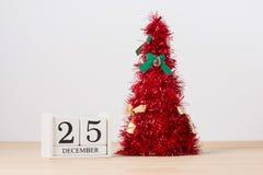 Roter Weihnachtsbaum auf Tabelle mit Kalender am 25. Dezember Stockbild