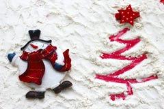 Roter Weihnachtsbaum gemalt auf Schnee und Schneemann Stockfotos