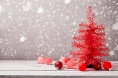 Roter Weihnachtsbaum mit Dekorationen auf Holztisch Stockfotografie