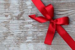 Roter Weihnachtsfarbbandbogen auf hölzernem Vorstand Stockbild