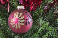 Roter Weihnachtsflitter, der an einem Baum hängt Stockfotografie