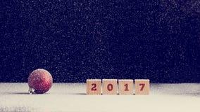 Roter Weihnachtsflitter und Reihe von vier Holzklötzen, die 2017 lesen Stockbild