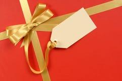Roter Weihnachtsgeschenkhintergrund, Goldbandbogen, leeres Manila-Geschenktag oder Aufkleber Stockbild