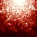 Roter Weihnachtshintergrund mit defocused Leuchten Stockfotografie