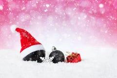 Roter Weihnachtshintergrund - verzierte schwarze Kugeln auf Schnee mit Schneeflocken und Sternen Lizenzfreie Stockfotos