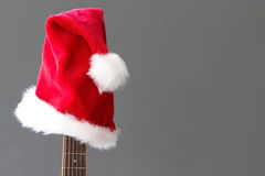 Roter Weihnachtshut auf Gitarre mit grauem Hintergrund Stockbilder