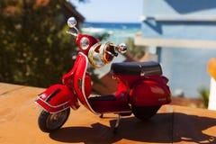 Roter Weinlesespielzeugroller oder -motorrad mit den Goldenen und Silberhochzeitringen auf ihm im Hintergrund der Seeansicht Stockfotos
