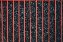 Roter Zaun auf der gr?nen Baumwand stockbild