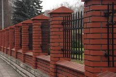 Roter Zaun hergestellt vom Ziegelstein mit Metallstangen lizenzfreie stockfotos