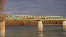 Roter Zug, der die Eisenbahnbrücke kreuzt lizenzfreies stockbild