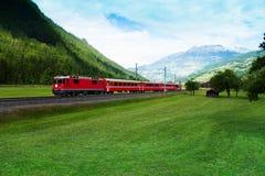 Roter Zug, der grünes Tal nahe Alpen kreuzt Lizenzfreie Stockfotografie