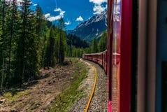 Roter Zug, der langsam zum Bernina-Durchlauf in den Schweizer Alpen klettert lizenzfreies stockbild