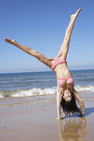 Roterande Cartwheel för kvinna på strandferie Arkivfoto