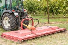 Roterande gräsklippningsmaskin på en liten traktor som odlar en fruktträdgård fotografering för bildbyråer