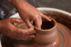 Roterande keramiker` s rullar och leraware p? den som tas fr?n ?ver Hugger hans h?nder med en lerakopp p? keramikers hjul royaltyfria foton