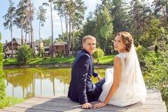 Roterande nygifta personer tillbaka och se kameran, medan sitta på wo royaltyfria bilder