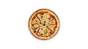 Roterande pizza med champinjoner blir rädd söta peppar och oliv på en träställning som isoleras på en vit bakgrund lager videofilmer