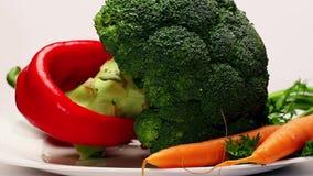 Roterande platta med nya grönsaker arkivfilmer