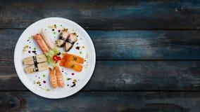 Roterande sashimiuppsättning på en vit rund platta som dekoreras med små blommor, japansk mat, bästa sikt spelrum med lampa stock video