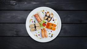 Roterande sashimiuppsättning på en vit rund platta som dekoreras med små blommor, japansk mat, bästa sikt Svart trä arkivfilmer