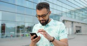 Roterande sikt av den stiliga le afrikanska mannen i glasögon som pratar och bläddrar på mobiltelefonen nära stock video
