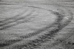 Roterande svarta gummihjulspår över den mörka asfaltvägen Arkivbild