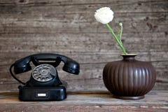 Roterande telefon bredvid en vit nejlikablomma Royaltyfri Bild