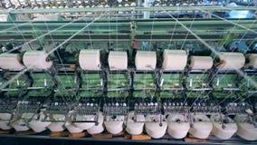 Roterande utrustning köar clews med vit fiber på en textilväxt stock video