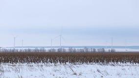 Roterande vindturbiner i avståndet i ett snöig fält arkivfilmer