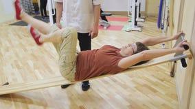 Roterar den äldre kvinnan för fysioterapeutportionen ben som gör övningar i konditionrum Sund gymnastik Aktivt folk lager videofilmer