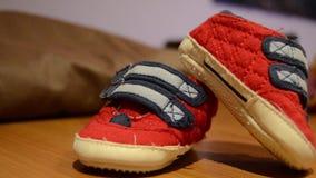 Roterend camera, sluit omhoog geschoten van baby rode en blauwe schoenen stock footage